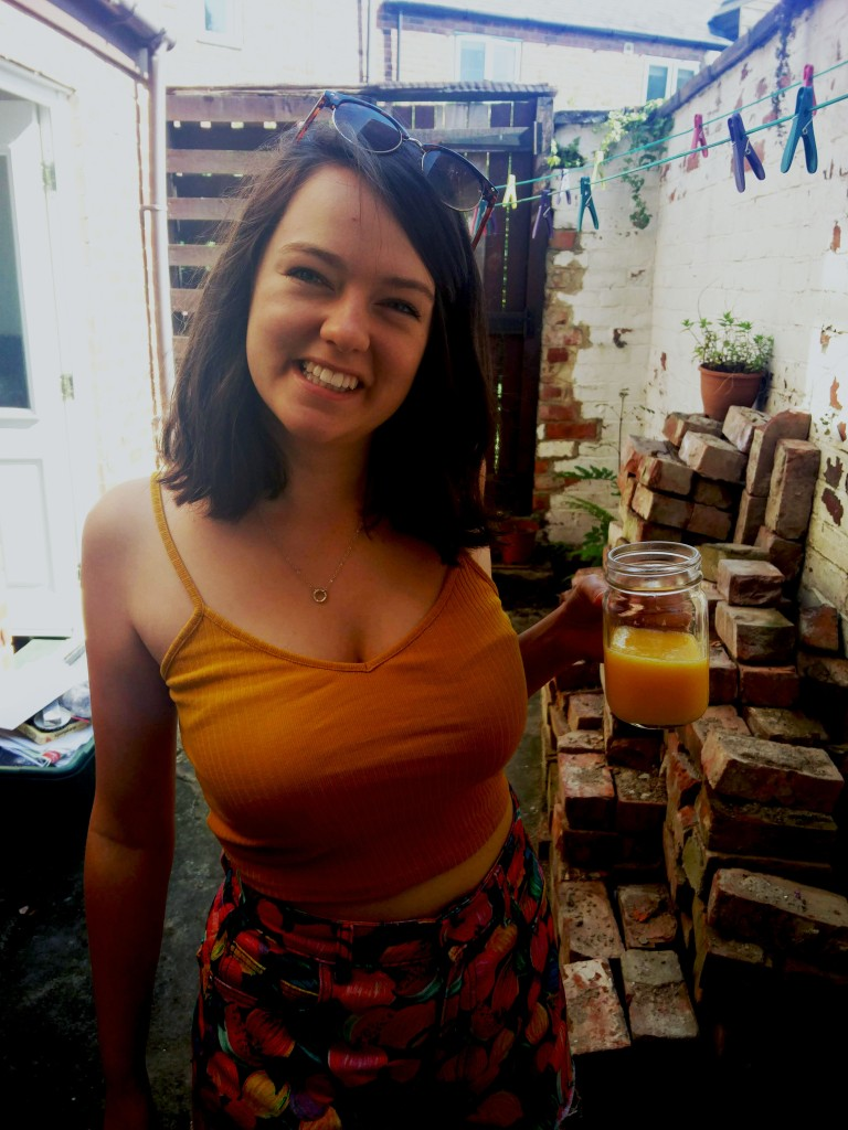 Me in the summer with some orange juice, outside our student house.